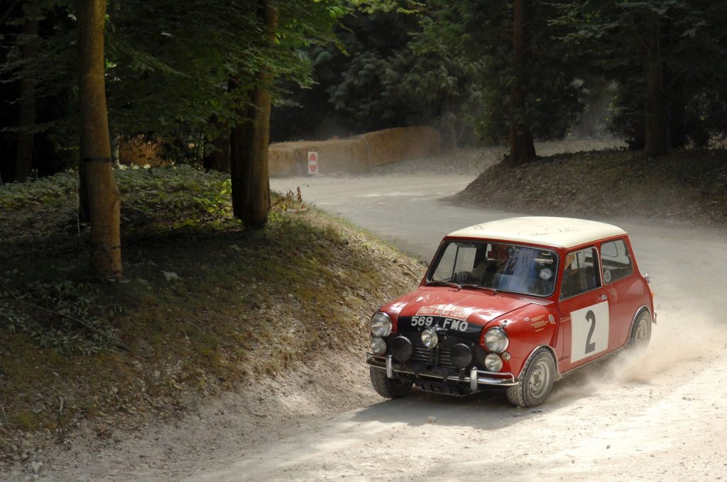 A classic red-and-white Austin Mini Cooper S drives around the 2009 Goodwood Festival of Speed Forest Rally Stage