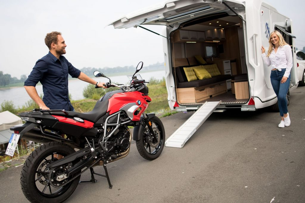 A man loads a red BMW motorcycle onto a white Knaus camper van RV with a ramp