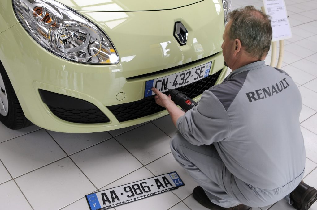 A mechanic installs a front license plate on a light-green 2009 Renault