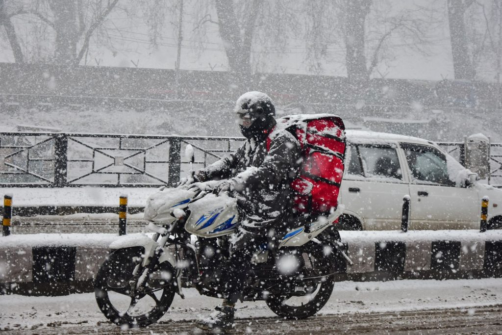 A black-clad motorcycle rider dressed in full winter gear rides through a Kashmir snowstorm