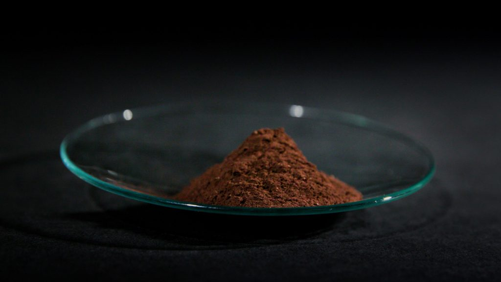 A pile of rust-colored rare-earth metal oxides recovered via Nissan's recycling process