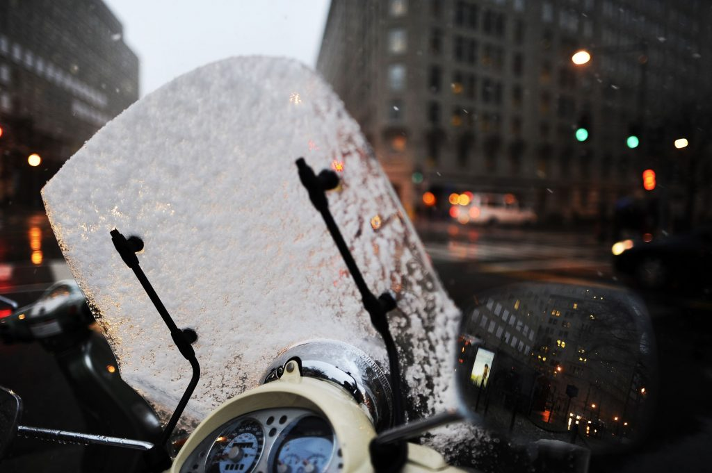 A snow-covered motorcycle windshield seen in Washington, DC
