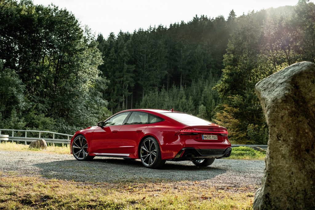 A red 2021 Audi RS7 luxury car shot in a forest from the rear 3/4 angle