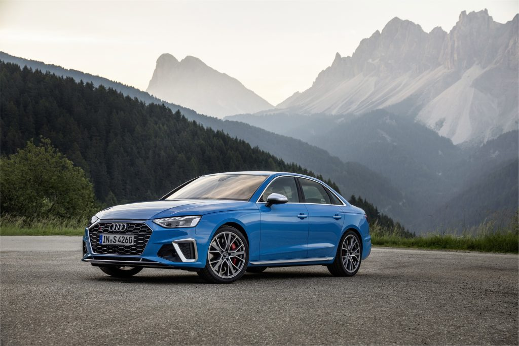 A blue Audi S4 sits parked on a jagged mountain pass