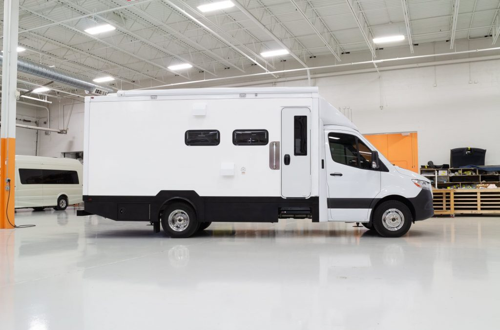 The side view of the white Advanced RV B Box 'Asteroid of Happiness' in the company's garage