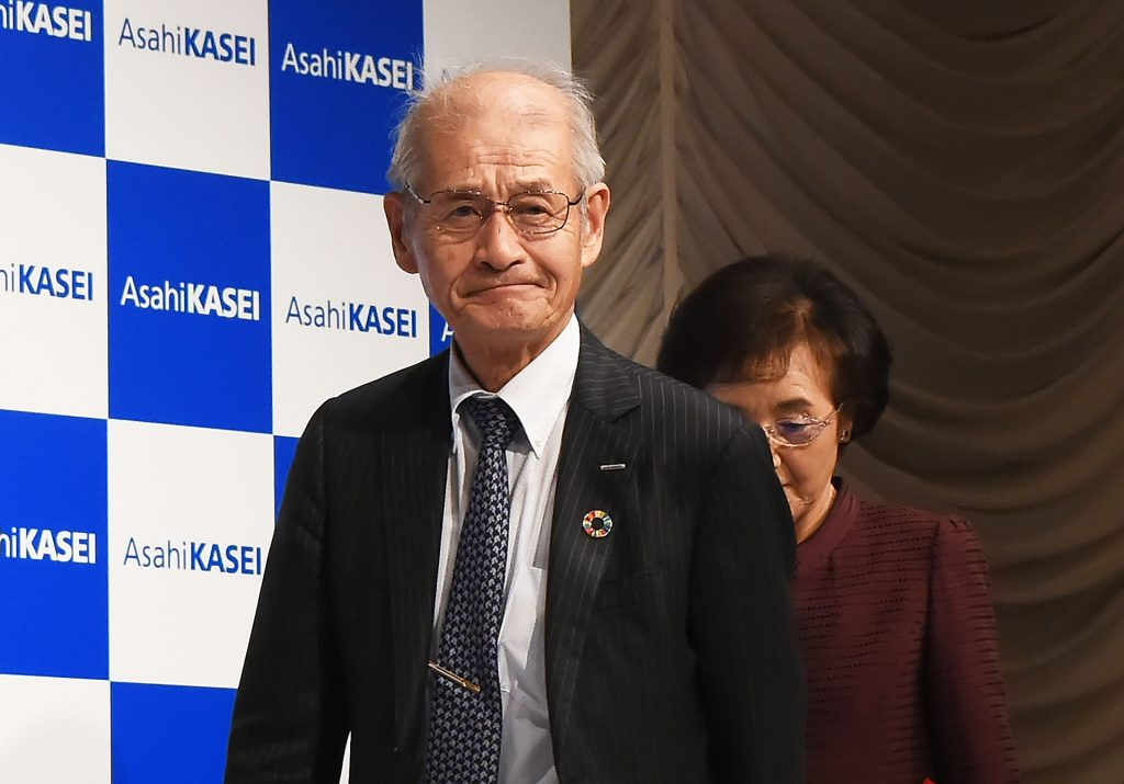 Scientist Akira Yoshino approaching a podium to address the press during a conference at the Inperial Hotel. Yoshino recently made comments that he believes the Apple Car will be revealed in 2021