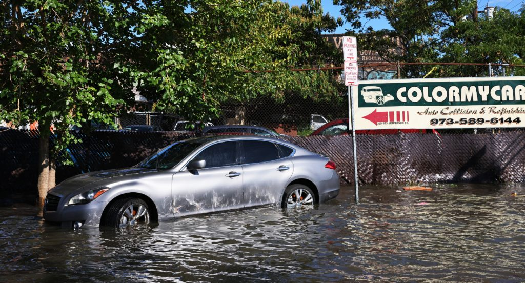 An abandoned car is seen in flooded waters.