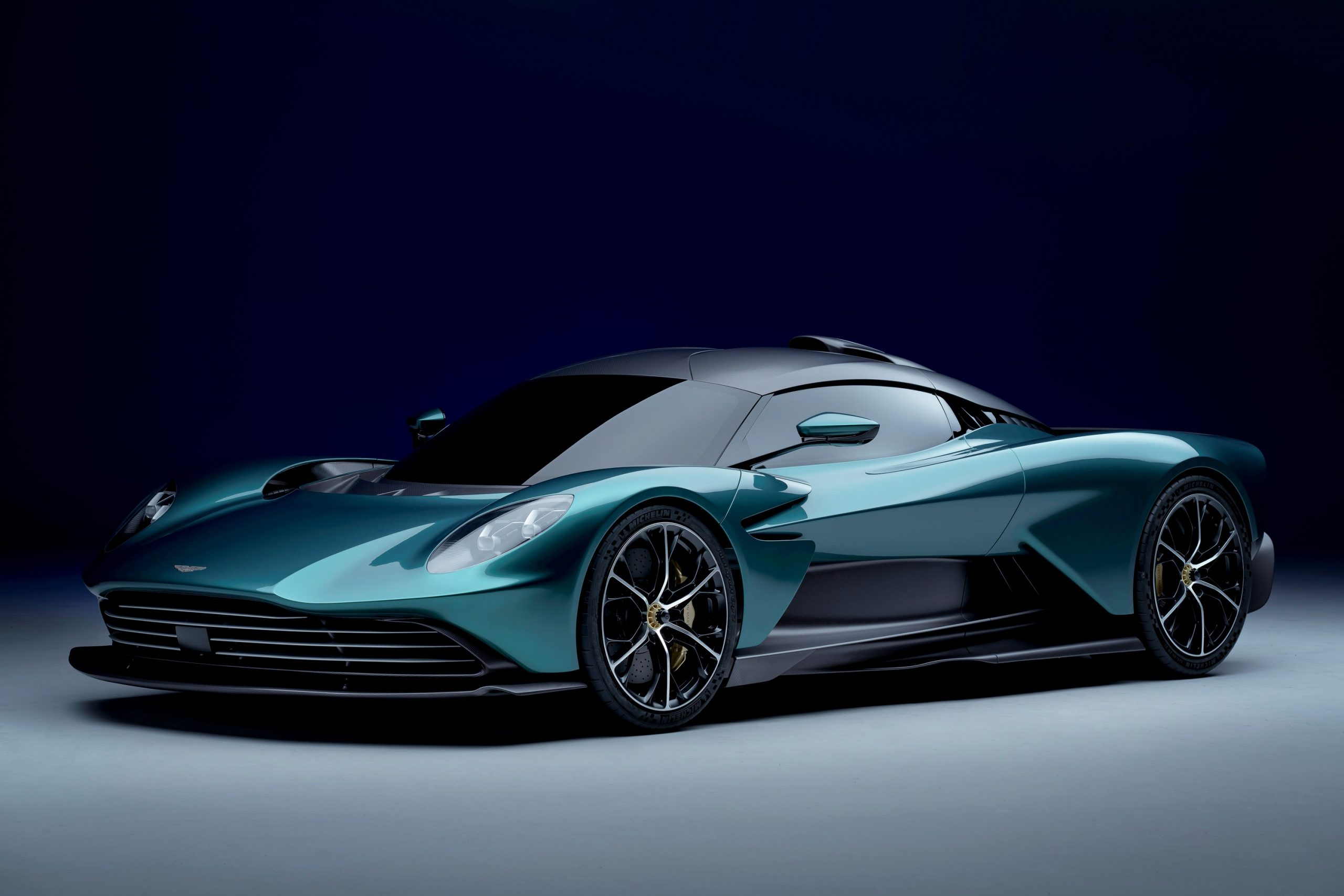 A green Aston Martin Valhalla shot from the front 3/4 angle in a studio