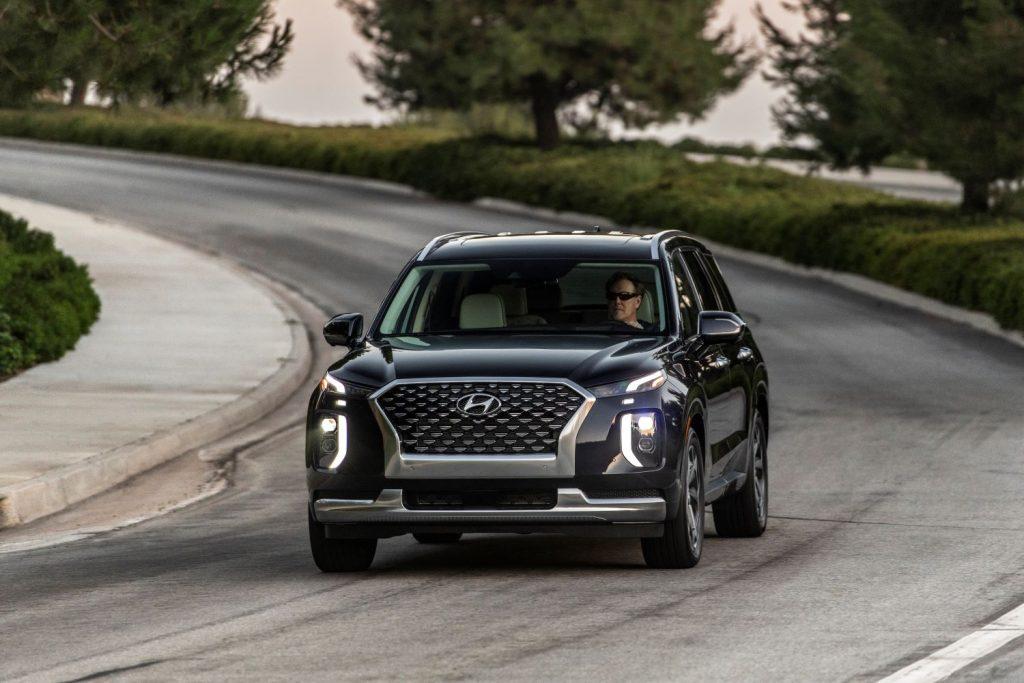 Black 2022 Hyundai Palisade driving on a curvy road