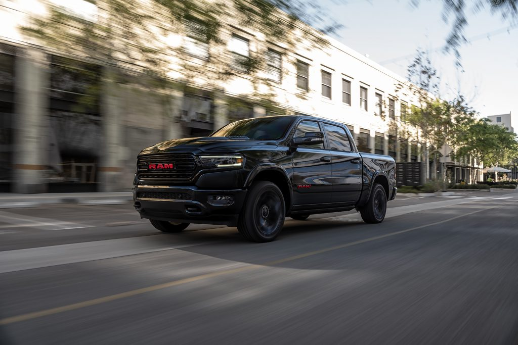 Black 2022 Ram 1500 Limited (RAM) RED Edition driving down a street