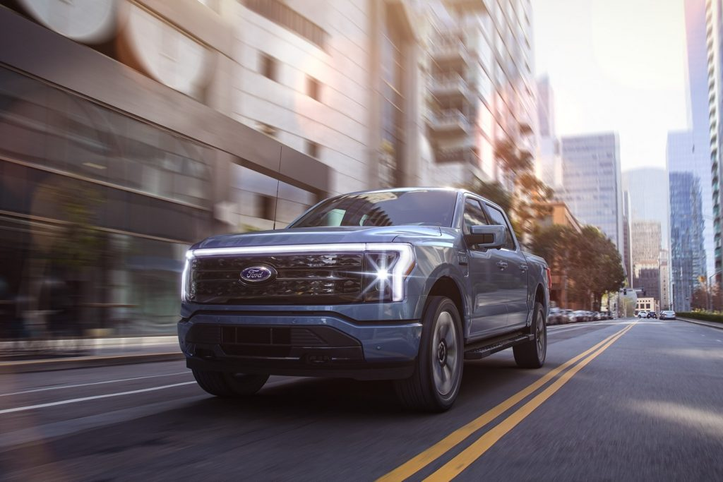 Blue 2022 Ford F-150 Lightning driving on a city street