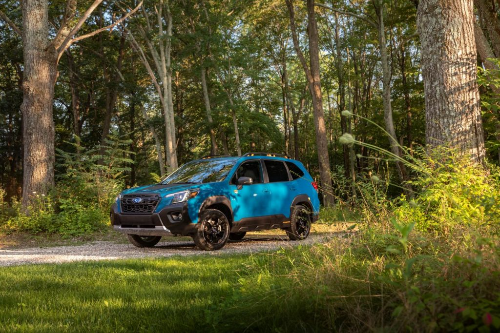 Blue 2022 Subaru Forester driving through a forest