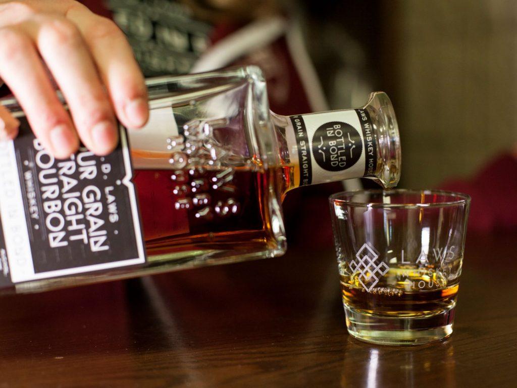 Bottle of Laws Four Grain bourbon poured into glass