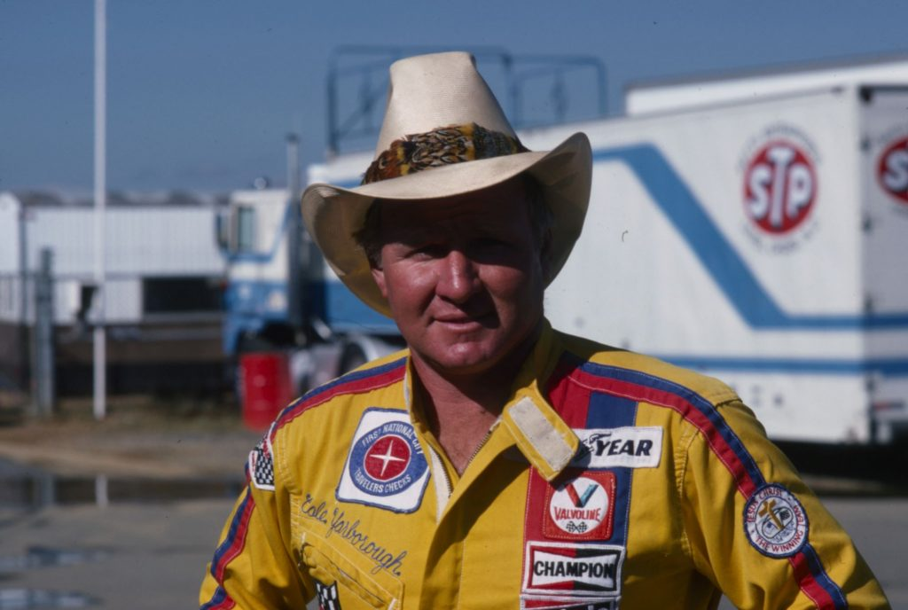 Cale Yarborough wearing a yellow shirt with carious branded patches.