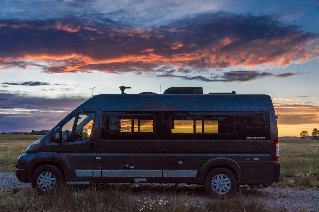 Camper Van Parked In Front Of Sunset