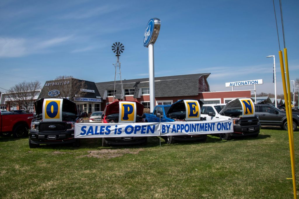"""Car dealership lot with a sign that says """"Open. Slaes is Open by appointment only."""""""