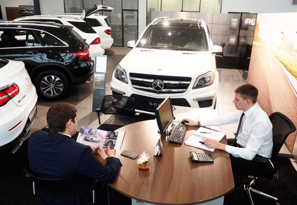 A car sales man sits with a customer at a dealership.