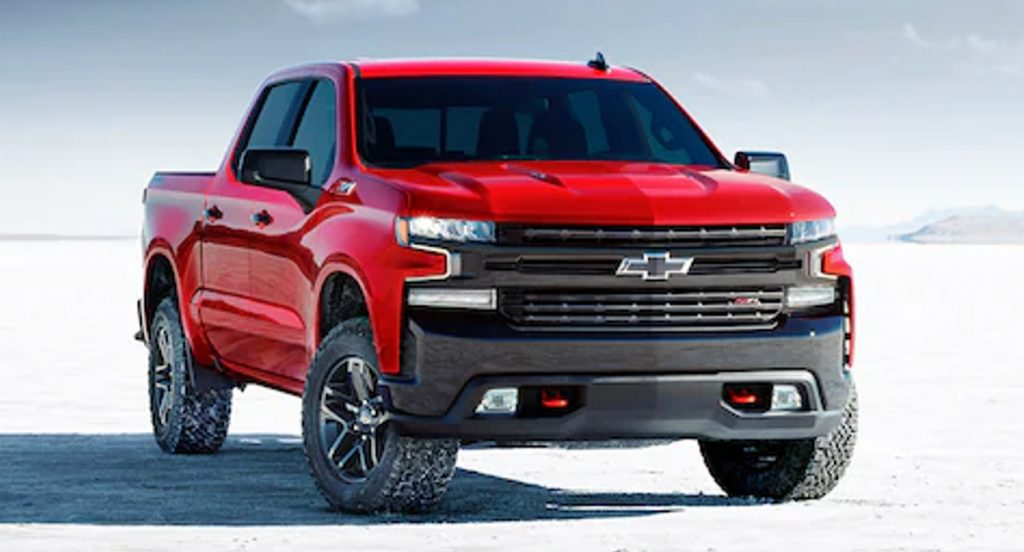 A red 2021 Chevrolet Silverado 1500 LT Trail boss is parked in ground lightly coated in snow.