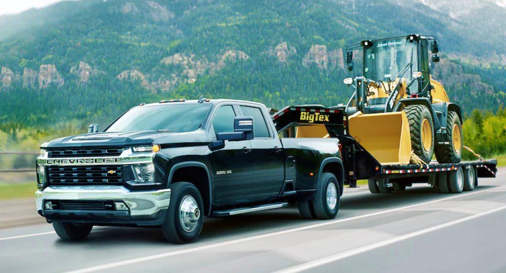 A black 2021 Chevrolet Silverado 3500 heavy duty pickup truck is towing a bulldozer.