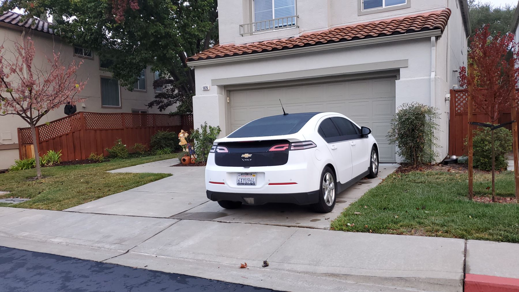 A Chevrolet Volt EV model parked outside the garage of a suburban home