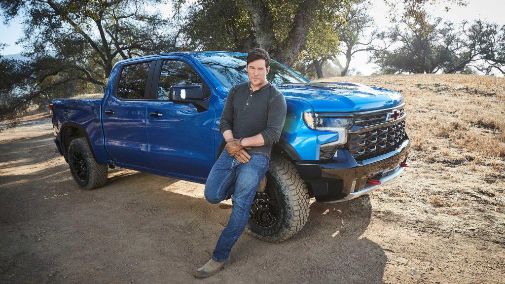 Chris Pratt leaning up against a blue 2022 Chevy Silverado ZR2