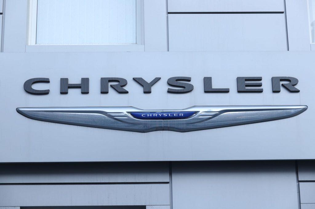 Silver, blue, and black Chrysler logo, maker of the Chrysler 300, on a white building.