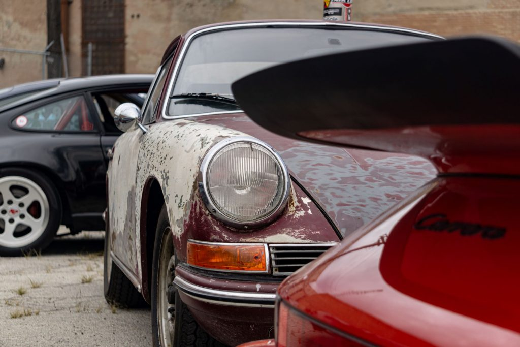 Classic early Porsche 911 with patina behind a red 1987 911 Carrera 3.2
