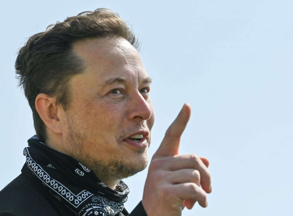 Creator of Tesla, Elon Musk dressed in black with a black handkerchief around his neck.