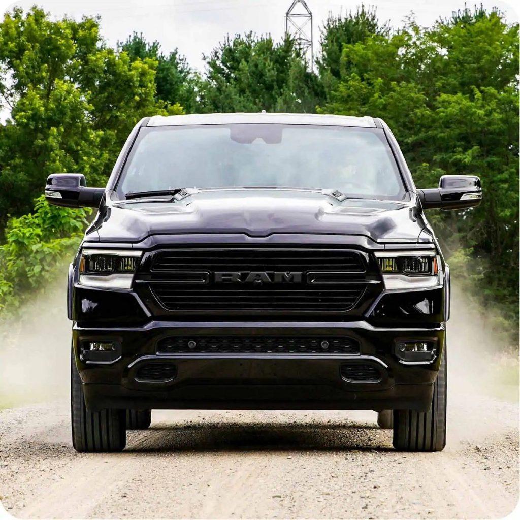 A black 2021 Ram 1500 driving down a dirt road.