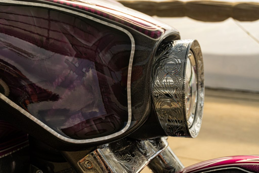 A close-up view of the engraved headlight on David Moreno's custom purple-and-black 2013 Harley-Davidson Street Glide