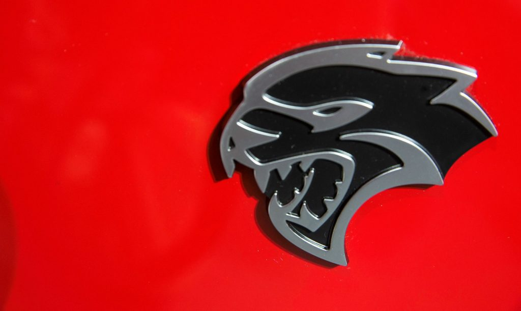 A Dodge Challenger Hellcat logo on a red car.