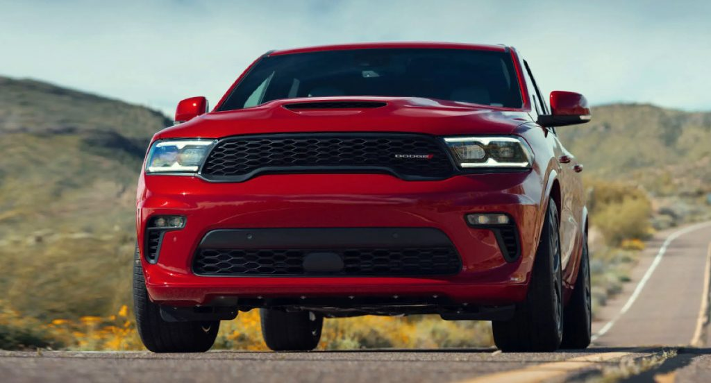 A red Dodge Durango SUV is driving on the road.