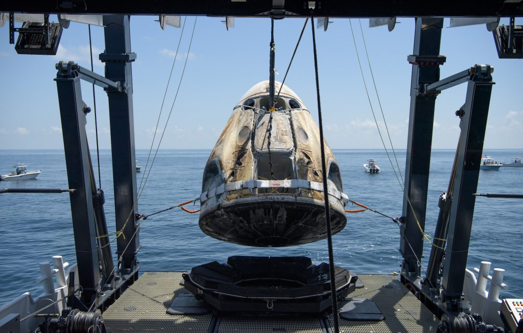 The SpaceX Crew Dragon Endeavour spacecraft is lifted onto the SpaceX GO Navigator recovery ship shortly after it landed with NASA