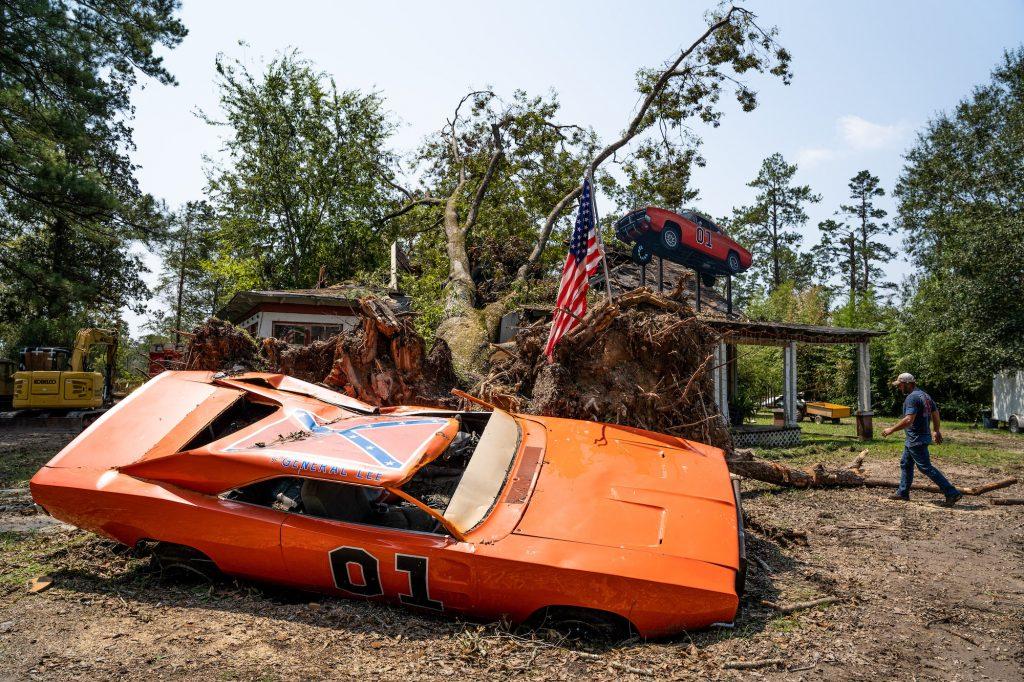 A man walks near a General Lee car, damaged by Hurricane Ida, at John Schneider Studios on September 2, 2021, in Holden, Louisiana