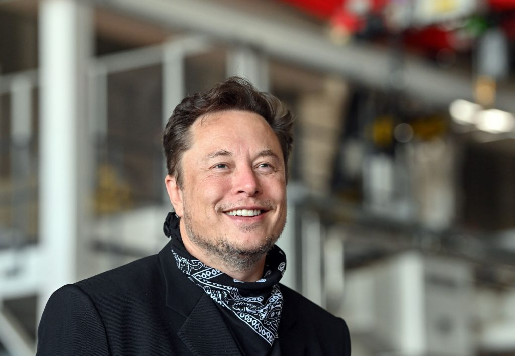 Elon Musk dressed all in black with a black and white handkerchief around his neck with industrial pipes in the background.