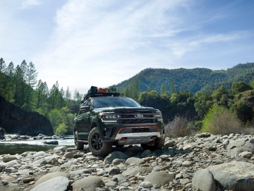 A  dark colored 2022 Ford Expedition Timberline climbs rocks next to a stream.