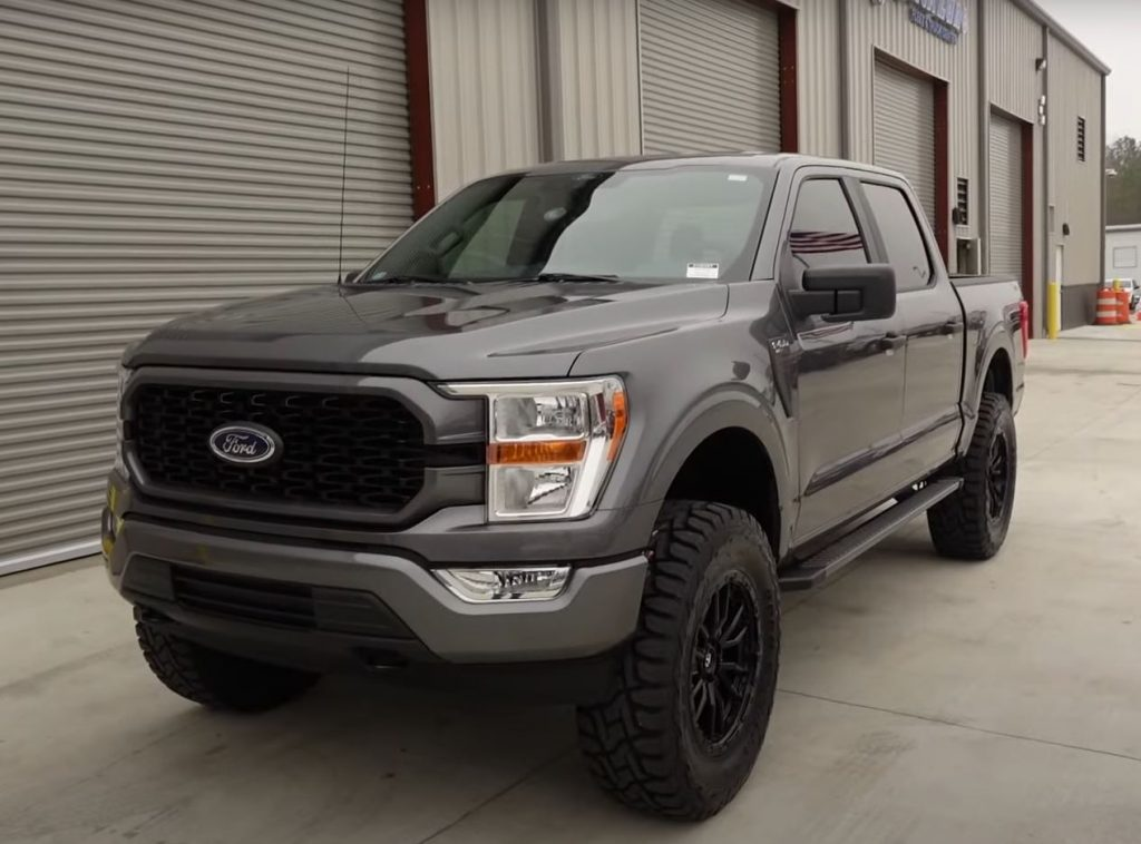A grey F-150 SuperCrew with a 6-inch lift parked outside