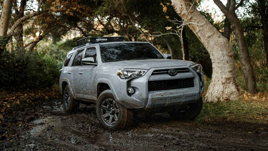 A white 2021 Toyota 4Runner drives through the woods.