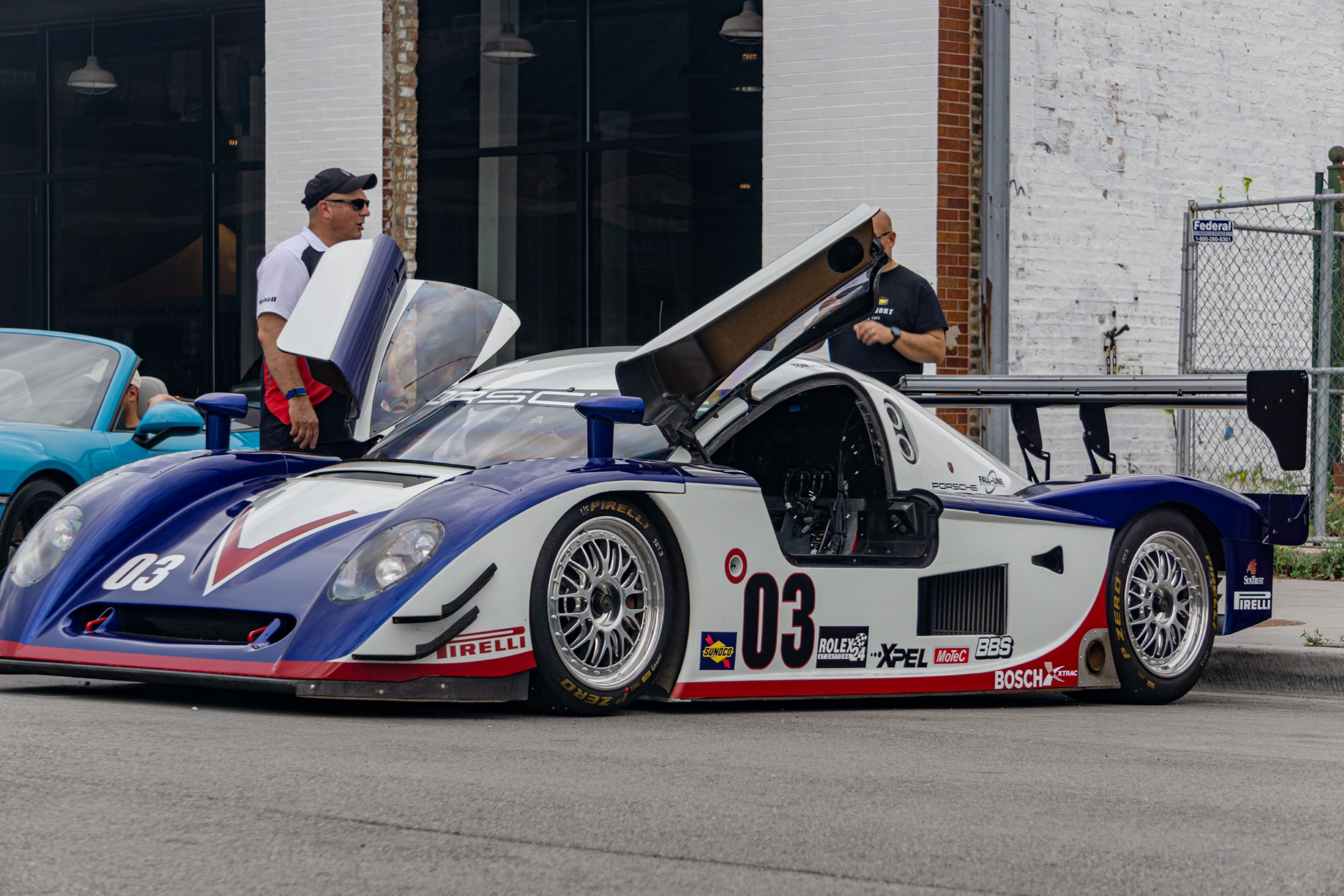 The front 3/4 view of Fall-Line Motorsports' white-blue-and-red Porsche Crawford Daytona Prototype with its left-side door open