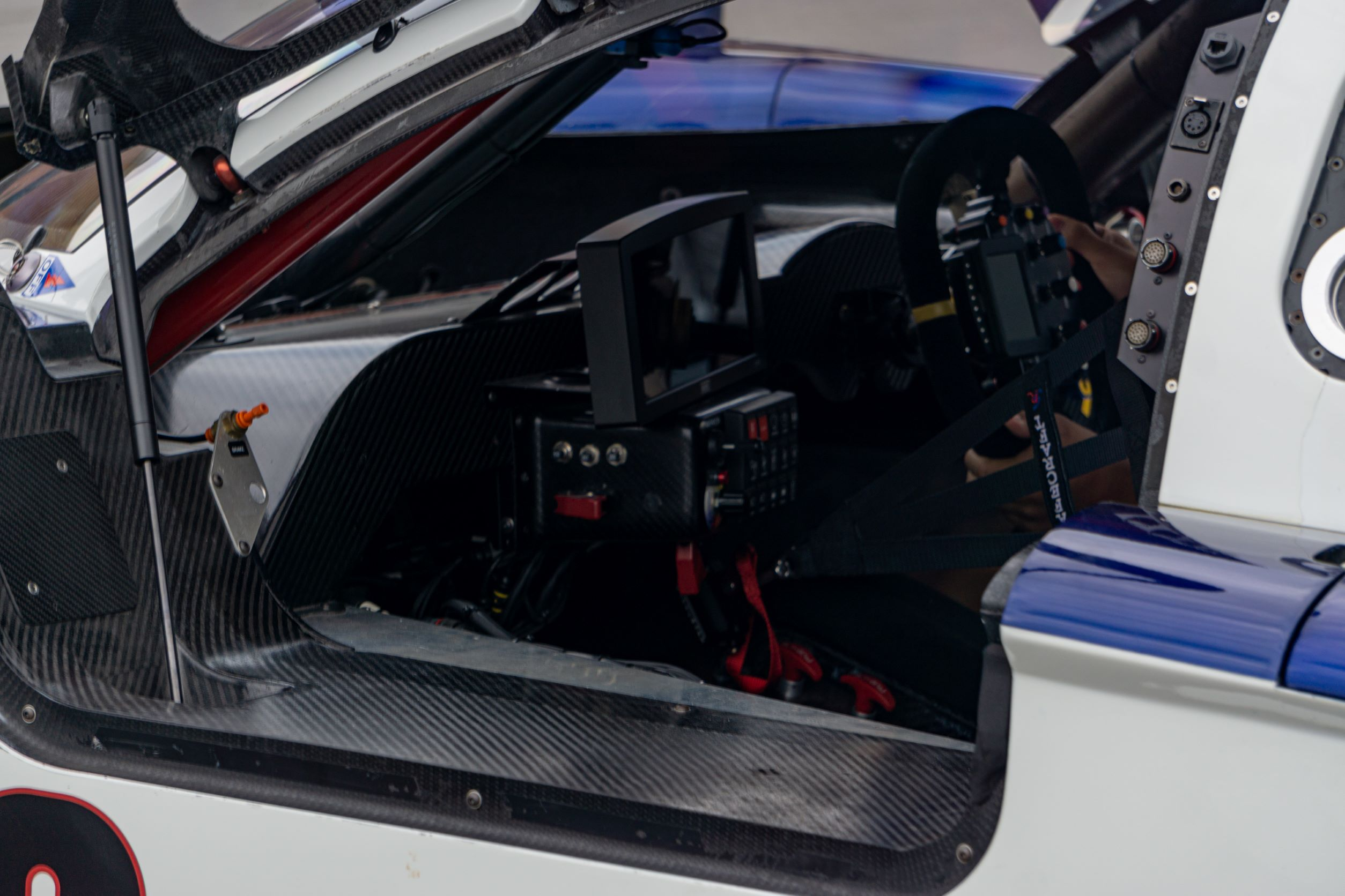 The carbon-fiber-heavy left-side interior view of Fall-Line Motorsports' white-red-and-blue Porsche Crawford Daytona Prototype