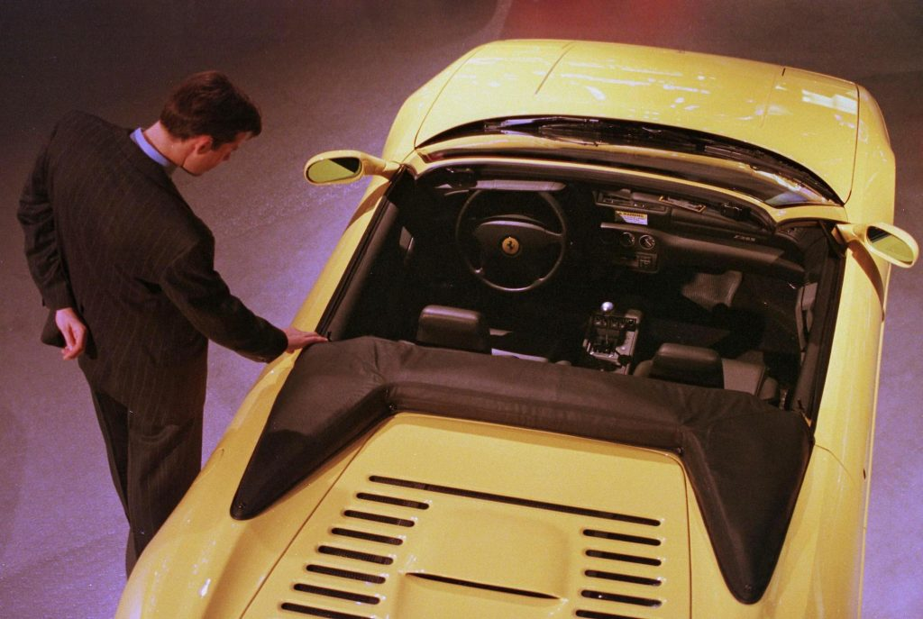 A passerby looks at a Ferrari F355 Spider at the 1998 North American International Auto Show in Detroit