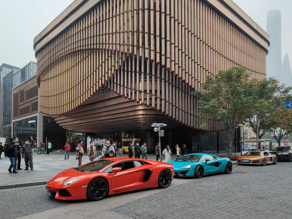 A red Ferrari and a light blue Lamborghini in front of a modern shaped tall building.