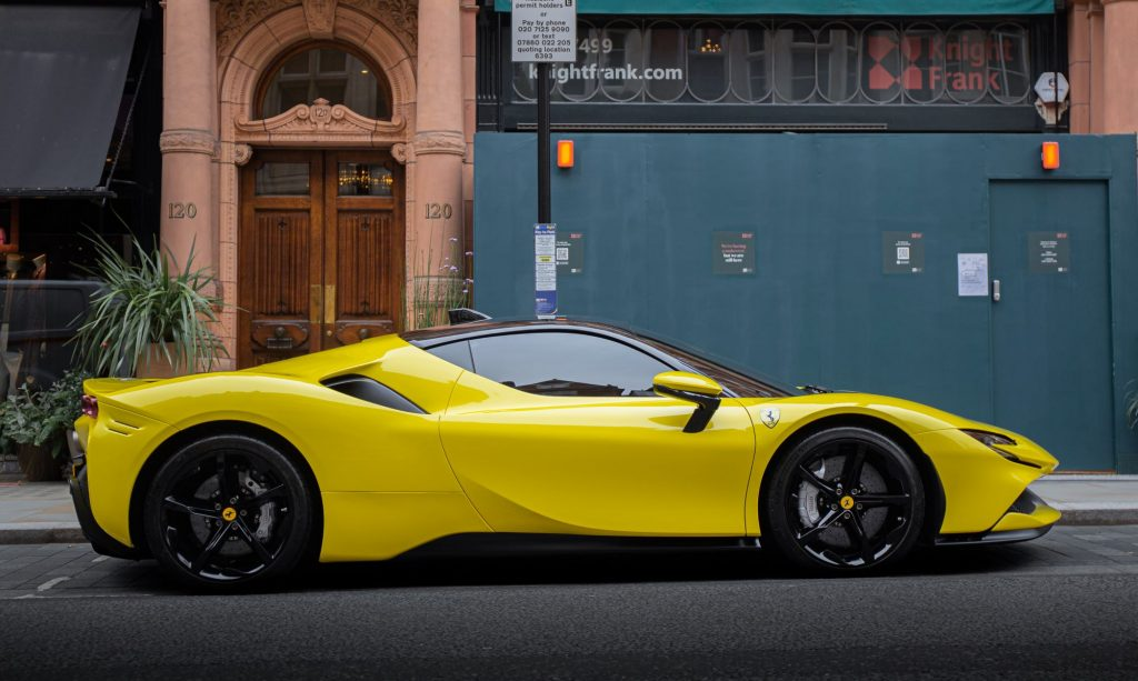 Yellow Ferrari SG90 sitting in front of a green and brown building on the curb.