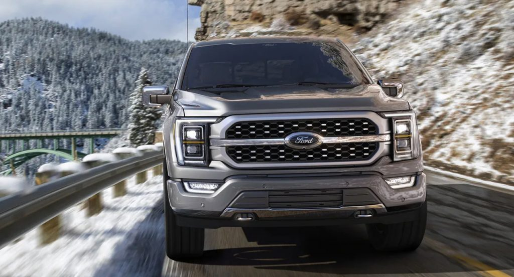 A gray Ford F-150 Lightning is driving on a snowy road.