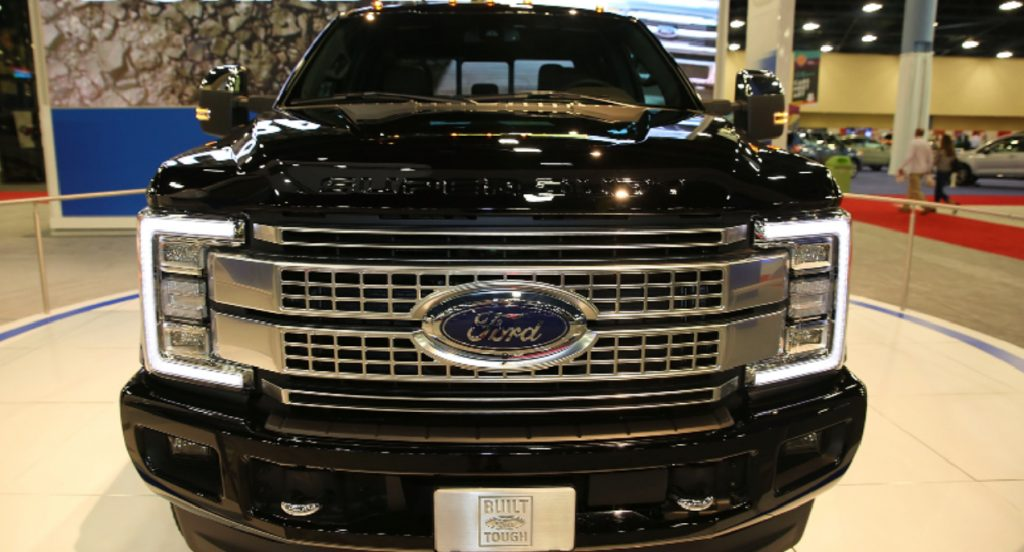 A black Ford F-250 heavy duty truck is on display.