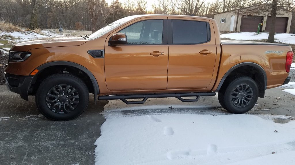 An orange Ford Ranger with nerf bars parked outside in snow