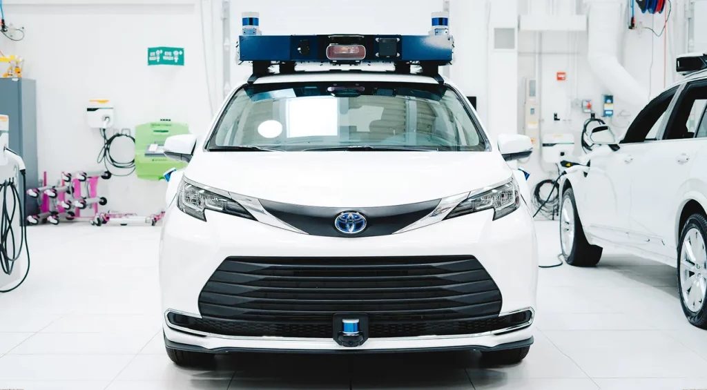 Front view of white Aurora Toyota Sienna self-driving taxi