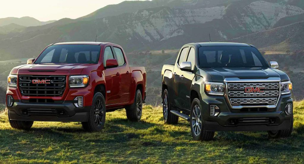 A red (left) and a black (right) GMC Canyon mid-size truck parked on a grassy plane in front of a beautiful horizon.