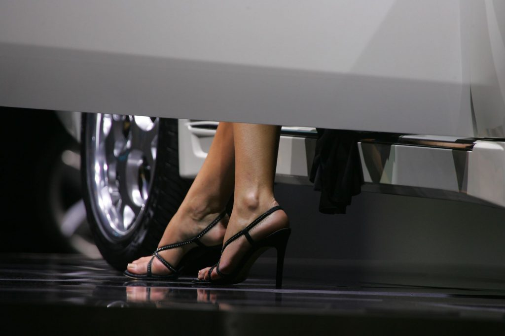 A person getting in to a car wearing a pair of black high heels.