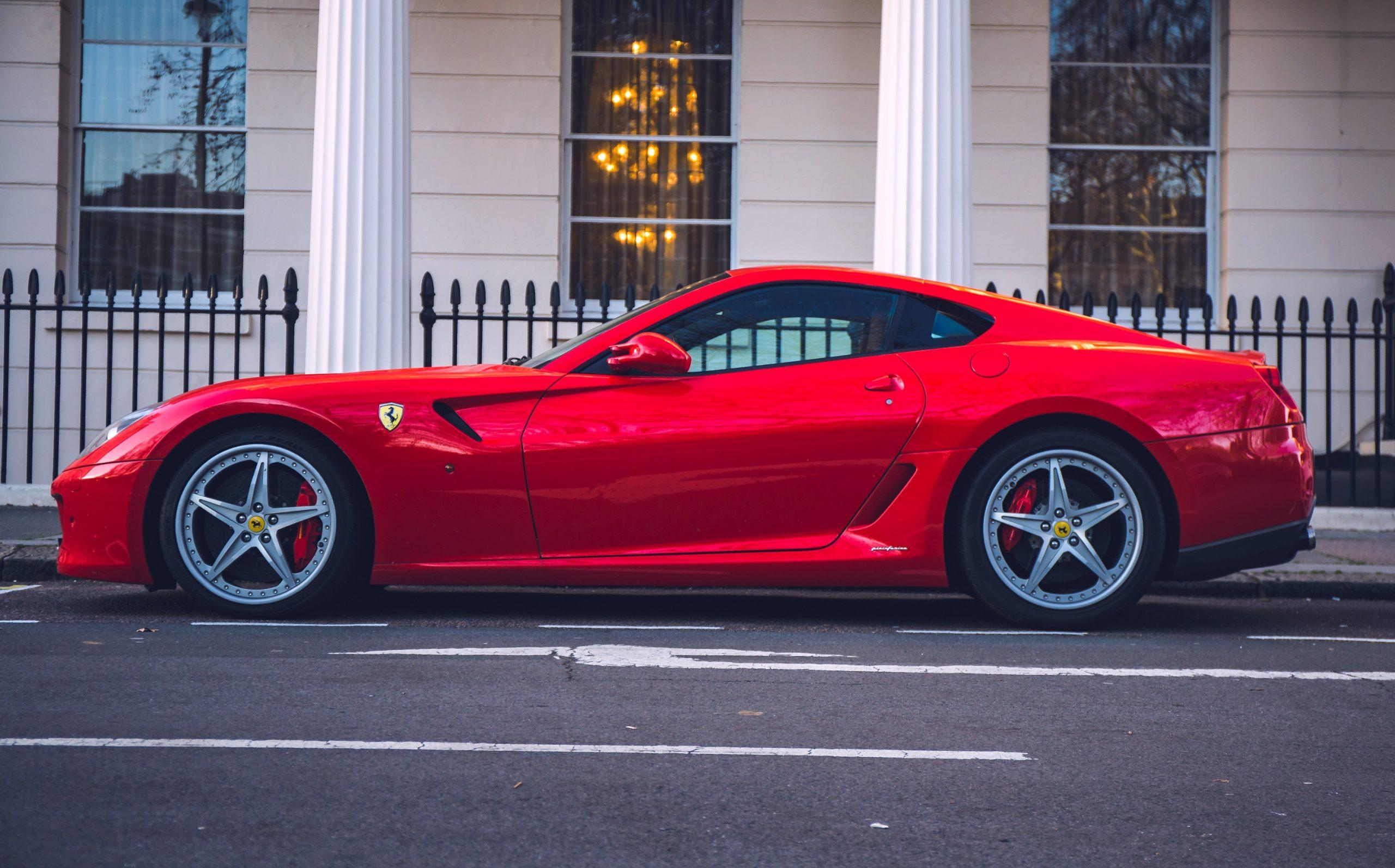 A red Ferrari 599 GTB shot in profile on a London side street